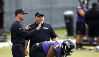 FILE - In this Aug. 8, 2017, file photo, Baltimore Ravens head coach John Harbaugh, left, speaks with then-senior offensive assistant/tight ends coach Greg Roman as offensive tackle Ronnie Stanley prepares to run a drill during an NFL football training camp practice in Owings Mills, Md. Roman is off to a running start in his new role as offensive coordinator of the Baltimore Ravens, working on a ground game that will coincide with the skills of agile quarterback Lamar Jackson. (AP Photo/Patrick Semansky) **FILE**