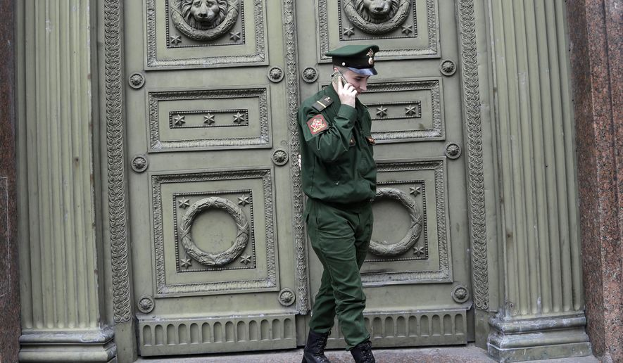 FILE  - In this file photo taken on Monday, July 9, 2018, a Russian soldier speaks on his smart phone during the 2018 soccer World Cup in St. Petersburg, Russia. Russian lawmakers have approved a bill prohibiting military personnel from using smartphones on duty, a move intended to block leaks of sensitive information on social media. (AP Photo/Petr David Josek, File)