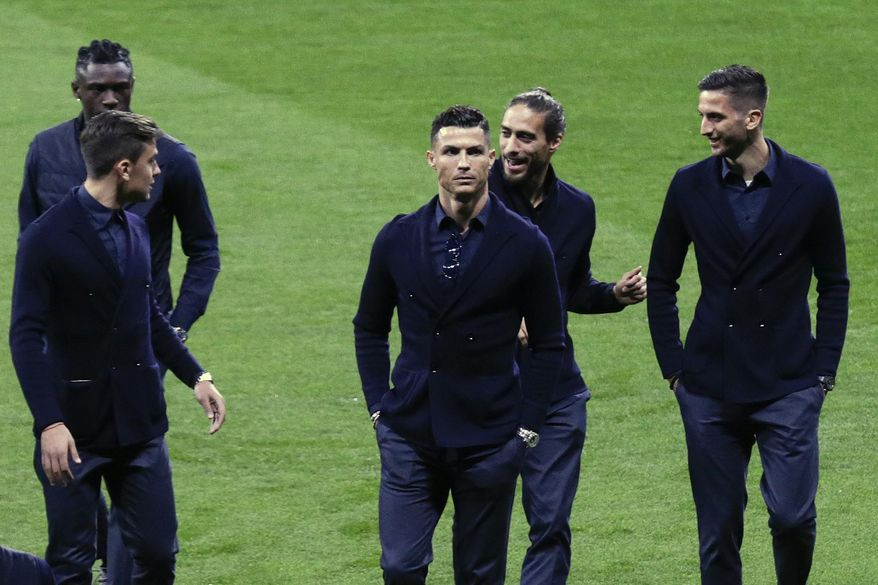 Juventus players Moise Kean, left, Paulo Dybala, second left, Cristiano Ronaldo, center, Martin Caceres and Rodrigo Bentancur, right, walk onto the pitch after their arrival at Wanda Metropolitano stadium in Madrid, Spain, Tuesday, Feb. 19, 2019. Juventus will play against Atletico Madrid in a first leg, round of sixteen, Champions League soccer match. (AP Photo/Andrea Comas)