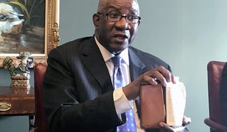 FILE - In this Aug. 17, 2018, file photo, Pulaski County Circuit Judge Wendell Griffen holds a copy of the U.S. Constitution at a news conference in Little Rock, Ark. The Supreme Court is leaving in place a decision dismissing a lawsuit filed by a judge in Arkansas who was barred from overseeing execution-related cases after he participated in an anti-death penalty demonstration. (AP Photo/Andrew DeMillo, File)