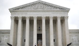 """In this Oct. 9, 2018 photo, police office guards the main entrance to the Supreme Court in Washington.  The Supreme Court has agreed to consider a case about the reach of a federal clean water law. The justices agreed Tuesday to hear a case involving the Clean Water Act. The act requires polluters to get a permit when they release pollution from a source such as a pipe or well to certain bodies of water such as rivers and lakes that are called """"navigable waters."""" The case involves treated wastewater from the Lahaina Wastewater Reclamation Facility in Hawaii.(AP Photo/Pablo Martinez Monsivais)"""