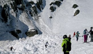 Rescue crews work work at the site of an avalanche site in the ski resort of Crans-Montana, Switzerland, Tuesday, Feb. 19, 2019. Swiss mountain rescue teams pulled out several people who were buried in a mid-afternoon avalanche Tuesday at the popular ski resort of Crans-Montana and were searching for others, police said.  (Denis Mentha/Keystone via AP)