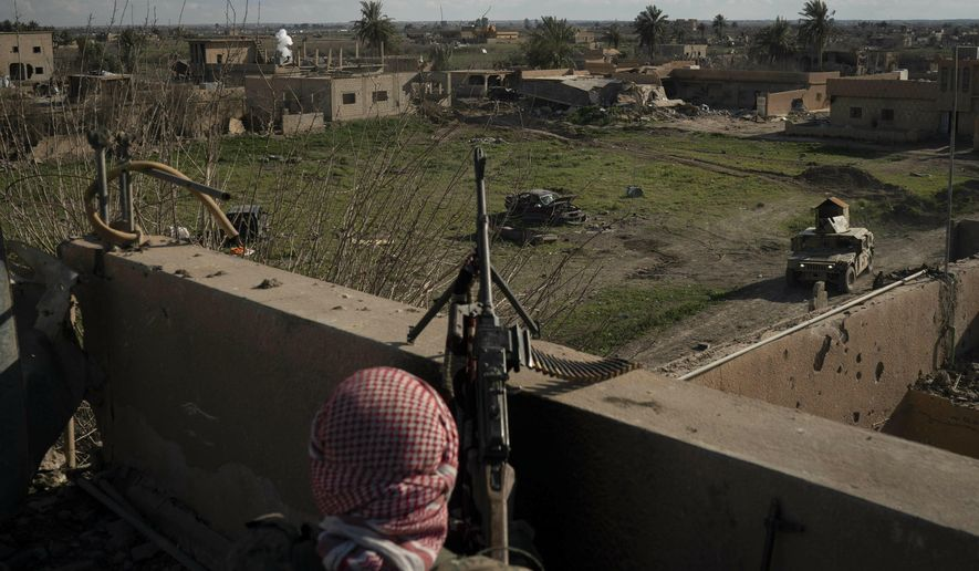A U.S.-backed Syrian Democratic Forces (SDF) fighter stands atop a building used as a temporary base near the last land still held by Islamic State militants in Baghouz, Syria, Monday, Feb. 18, 2019. Hundreds of Islamic State militants are surrounded in a tiny area in eastern Syria are refusing to surrender and are trying to negotiate an exit, Syrian activists and a person close to the negotiations said Monday. (AP Photo/Felipe Dana)