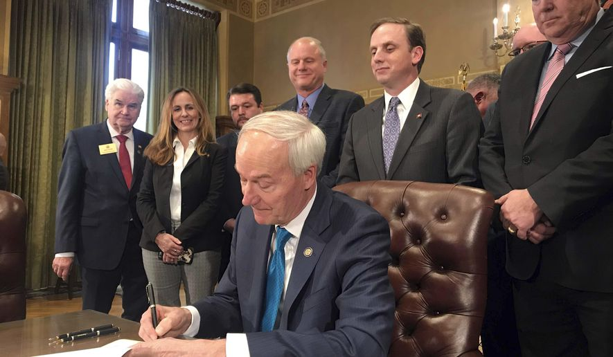 Arkansas Gov. Asa Hutchinson signs into law a $97 million plan to cut the state's top income tax rate during a ceremony at the state Capitol in Little Rock, Ark., on Tuesday, Feb. 19, 2019. (AP Photo/Andrew DeMillo)