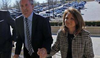 "FILE - In this Feb. 16, 2017, file photo, Texas Attorney General Ken Paxton, left, arrives at the Collin County Courthouse with his wife Angela in McKinney, Texas. The wife of Texas Attorney General says a bill she filed that would change state securities law ""literally has nothing to do"" with her husband's criminal case on charges of defrauding investors. Republican state Sen. Angela Paxton, who was elected in November, said Tuesday, Feb. 19, 2019, that she didn't consult with her husband on the bill, which calls for the attorney general's office to create a framework that would let entrepreneurs test some financial products and services without a license. (Jae S. Lee/The Dallas Morning News via AP, File)"