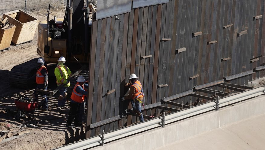 In this Tuesday, Jan. 22, 2019, photo, workers place sections of metal wall as a new barrier is built along the Texas-Mexico border near downtown El Paso. Such barriers have been a part of El Paso for decades and are currently being expanded, even as the fight over President Donald Trump's desire to wall off the entire U.S.-Mexico border has sparked the longest government shutdown in the nation's history. (AP Photo/Eric Gay)