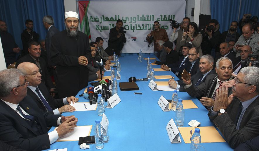 Algerian opposition leaders attend a political meeting with Abdallah Djaballah, standing at left, president of Algeria's Justice and Development Front, an Islamist party, in Algiers, Wednesday, Feb.20, 2019. Sectors of Algeria's diverse political opposition are meeting Wednesday to secure a joint candidate to face incumbent President Abdelaziz Bouteflika in the April 18 presidential election. (AP Photo/Anis Belghoul)