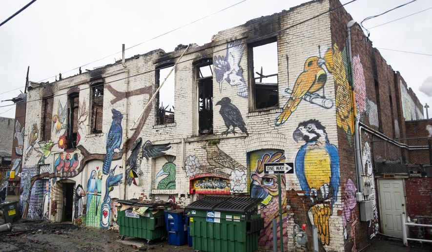 """In this photo taken Tuesday, Feb. 19, 2019, the charred remains of the """"Bird Alley"""" mural sit in the alley behind Holh Feed & Seed in Bellingham, Wash. The Bellingham Fire Department was called to a two-alarm fire early Monday morning that destroyed the second story and the granary tower of the building. More than 75 animals were rescued from a burning pet supply store. (Lacey Young/The Bellingham Herald via AP)"""
