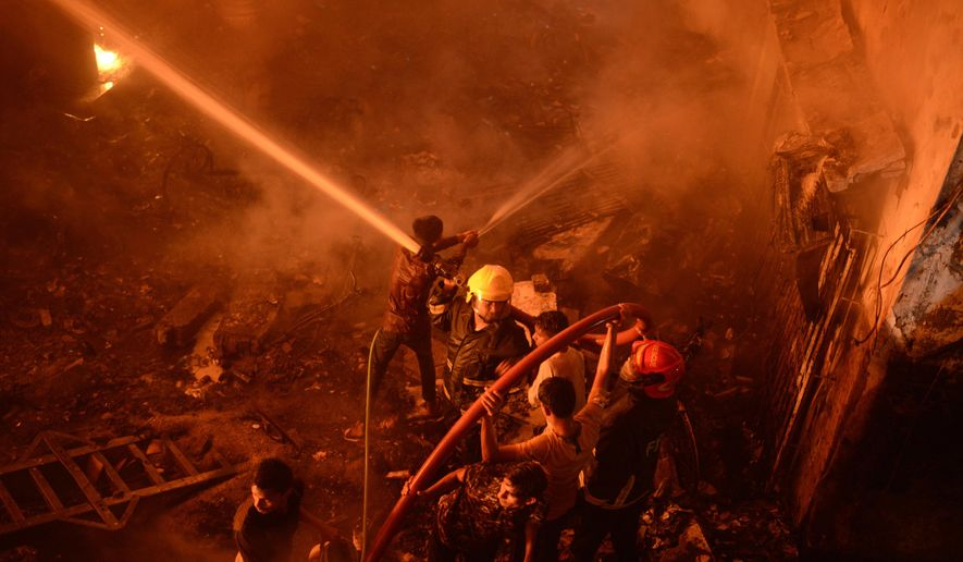 In this Wednesday, Feb. 20, 2019, photo, firefighters try to douse flames in Dhaka, Bangladesh. A devastating fire raced through at least five buildings in an old part of Bangladesh's capital and killed scores of people. (AP Photo)
