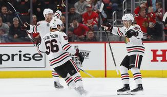 Chicago Blackhawks right wing Patrick Kane, right, celebrates his goal in overtime of an NHL hockey game against the Detroit Red Wings, Wednesday, Feb. 20, 2019, in Detroit. Chicago won 5-4. (AP Photo/Paul Sancya)