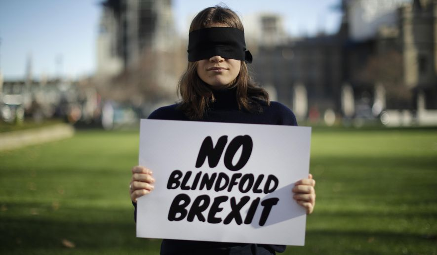 """Lara Spirit, aged 22 from Chichester, a remain in the European Union supporter and member of the """"Our Future, Our Choice"""" (OFOC) young people against Brexit organisation campaigning for a People's Vote second referendum on Britain's EU membership, poses for photographs after taking part in a protest against a blindfold Brexit on Parliament Square opposite the Houses of Parliament in London, Thursday, Feb. 14, 2019.  Lara believes a People's Vote second referendum would be the best way forward. Britain voted to leave Europe in a referendum more than two years ago, but Parliament has been unable to agree on a withdrawal arrangement, prompting some calls for a delay or even a cancellation of the split. (AP Photo/Matt Dunham)"""
