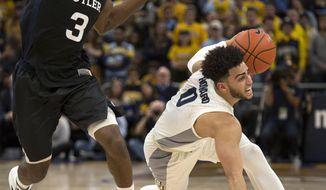 Marquette's Marcus Howard, right, slips as he drives past Butler's Kamar Baldwin, left, during the first half of an NCAA college basketball game Wednesday, Feb. 20, 2019, in Milwaukee. (AP Photo/Darren Hauck)