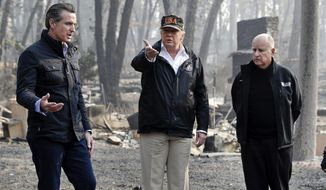"""FILE - In this Nov. 17, 2018, file photo, President Donald Trump talks with then Gov.-elect Gavin Newsom, left, and as California Gov. Jerry Brown listens during a visit to a neighborhood impacted by the wildfires in Paradise, Calif. California Gov. Gavin Newsom says the Trump administration is engaging in """"political retribution"""" by trying to take back $3.5 billion granted for the state's high-speed rail project. The Democratic governor says President Donald Trump is reacting to California suing over Trump's emergency declaration to pay for a wall along the U.S.-Mexico border. (AP Photo/Evan Vucci, File)"""