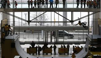 FILE - In this April 10, 2015 file photo, spectators watch a cyclist perform on a half pipe at COBO Center in Detroit. Officials say Detroit's Cobo Center will change its name, removing the surname of a former mayor known for his racist policies. The Detroit Regional Convention Facility Authority announced Wednesday, Feb. 20, 2019, that it has sold Cobo Center's naming rights to Detroit-based Chemical Bank in a 22-year deal that will generate $1.5 million annually. The new name will be announced later this year.  (AP Photo/Paul Sancya, File)