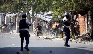 National police shoot at protesters demanding the resignation of Haitian President Jovenel Moise near the presidential palace in Port-au-Prince, Haiti, Wednesday, Feb. 13, 2019. Protesters are angry about skyrocketing inflation and the government's failure to prosecute embezzlement from a multi-billion Venezuelan program that sent discounted oil to Haiti. (AP Photo/Dieu Nalio Chery)