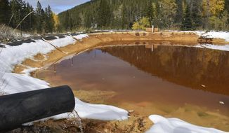 In this Oct. 12, 2018, file photo, water contaminated with arsenic, lead and zinc flows from a pipe out of the Lee Mountain mine and into a holding pond near Rimini, Mont. The community is part of the Upper Tenmile Creek Superfund site, where dozens of abandoned mines have left water supplies polluted and residents must use bottled water. (AP Photo/Matthew Brown)