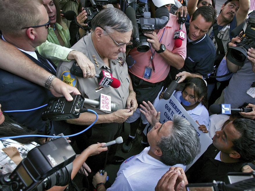 FILE - In this July 14, 2006, file photo, Elias Bermudez, lower right, kneels before then-Sheriff Joe Arpaio at a protest over the lawman's immigration crackdowns. Bermudez, who led the pro-immigrant group Immigrants Without Borders, is scheduled to be sentenced Wednesday, Feb. 20, 2019, in Phoenix for a felony conviction stemming from his tax preparation business. (AP Photo/Matt York, File)