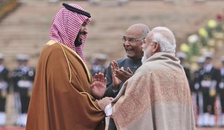 Saudi Arabia's Crown Prince Mohammed bin Salman interacts with Indian Prime Minister Narendra Modi, right, and President Ram Nath Kovind during a ceremonial welcome in New Delhi, India, Wednesday, Feb. 20, 2019. Prince Mohammed arrived in India after visiting Pakistan, which New Delhi blames for a suicide bombing attack last week that killed at least 40 Indian soldiers in disputed Kashmir. (AP Photo/Manish Swarup)