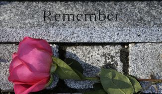 FILE - In this Feb. 20, 2018 file photo, a flower rests near a memorial to a victim of the Station nightclub fire following in West Warwick, R.I. The Feb. 20, 2003, fire that killed 100 and injured more than 200 others, started when pyrotechnics for the rock band Great White set fire to flammable foam installed as soundproofing. The site of the fire is now a memorial park. (AP Photo/Steven Senne, File)