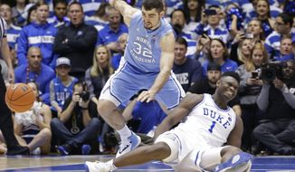Duke's Zion Williamson (1) falls to the floor with an injury while chasing the ball with North Carolina's Luke Maye (32) during the first half of an NCAA college basketball game in Durham, N.C., Wednesday, Feb. 20, 2019. (AP Photo/Gerry Broome) ** FILE **