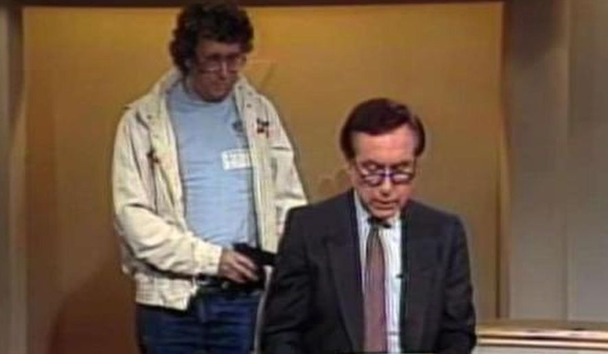 This Aug. 20, 1987, image made from video shows an intruder with a gun, as journalist David Horowitz is taken hostage during a live broadcast of Channel 4 Los Angeles. Horowitz remained calm and read the gunman's statements on camera, but the station had cut the broadcast without the gunman becoming aware of that fact. The gun turned out to be a toy BB gun, and Horowitz then took on the campaign to ban toy guns that look like real guns. Longtime consumer journalist David Horowitz has died at age 81, his wife told NBC4. (NBC-TV via AP)