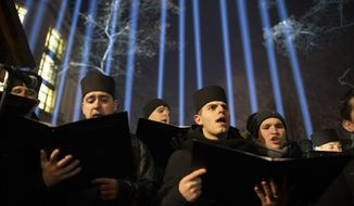 The Ukrainian Greek Catholic Church choir sings while paying their respect,  at a memorial dedicated to people who died in clashes with security forces at the Independent Square (Maidan) in Kiev, Ukraine, Wednesday, Feb. 20, 2019. Ukrainians mark the fifth anniversary of the violent Maidan protests. (AP Photo/Evgeniy Maloletka)