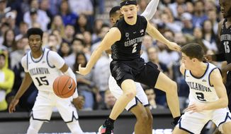 Georgetown guard Mac McClung, center, loses the ball against Villanova guard Collin Gillespie, right, and forward Saddiq Bey, left, during the first half of an NCAA college basketball game, Wednesday, Feb. 20, 2019, in Washington. (AP Photo/Nick Wass)