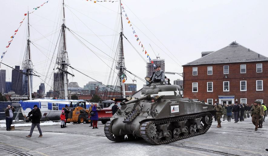 World War II tank gunner Clarence Smoyer sits atop a tank as he passes the historic frigate USS Constitution at the Charlestown Naval Shipyard in Boston, Wednesday, Feb. 20, 2019. The 95-year-old veteran was surprised with a ride through the streets of Boston in a Sherman tank, one of the tanks most widely used by the U.S. during the war. (AP Photo/Charles Krupa) ** FILE **