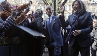 Civil rights leader Rev. Al Sharpton escorts Democratic presidential candidate Sen. Kamala Harris, D-Calif., right, past media and well wishers as they arrive for a lunch meeting at Sylvia's Restaurant in the Harlem neighborhood of New York, Thursday Feb. 21, 2019. (AP Photo/Bebeto Matthews)