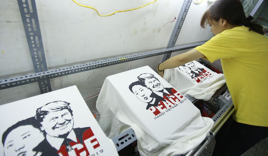 A worker removes t-shirts printed with portraits of U.S. President Donald Trump, right on shirt, and North Korean leader Kim Jong Un, at a custom t-shirt shop in Hanoi, Vietnam, on Thursday, Feb. 21, 2019. Hanoi is gearing up to host the second Trump-Kim summit scheduled for 27-28 February. (AP Photo/Hau Dinh)