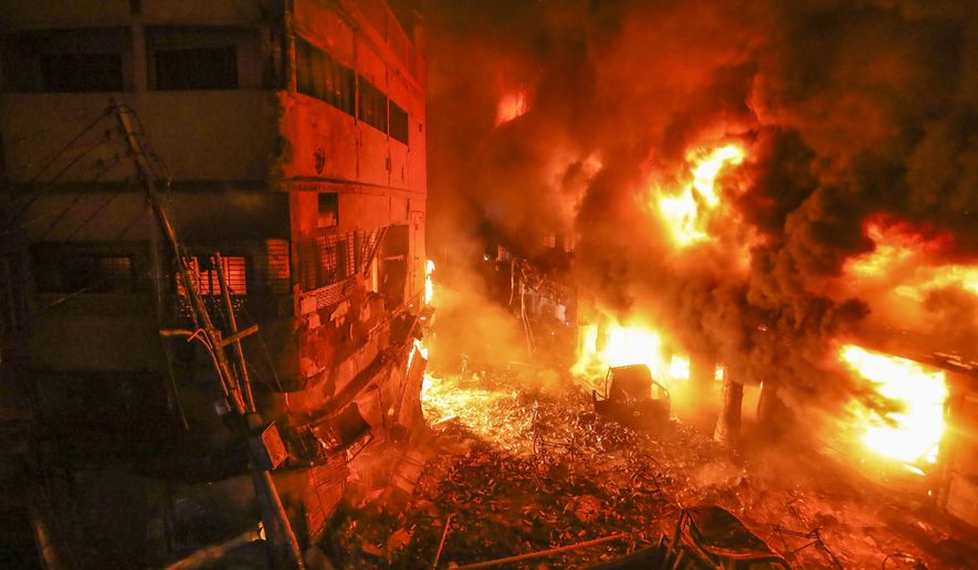 Flames rise from a fire in a densely packed shopping area in Dhaka, Bangladesh, Thursday, Feb. 21, 2019. A devastating fire raced through at least five buildings in an old part of Bangladesh's capital and killed scores of people. (AP Photo/Zabed Hasnain Chowdhury)