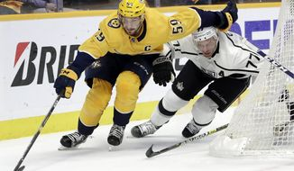 Nashville Predators defenseman Roman Josi (59), of Switzerland, moves the puck as Los Angeles Kings center Jeff Carter (77) follows during the first period of an NHL hockey game Thursday, Feb. 21, 2019, in Nashville, Tenn. (AP Photo/Mark Humphrey)