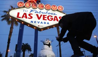 A man, who declined to give his name, takes a picture of a small snowman at the 'Welcome to Fabulous Las Vegas' sign along the Las Vegas Strip, Thursday, Feb. 21, 2019, in Las Vegas. (AP Photo/John Locher) **FILE**