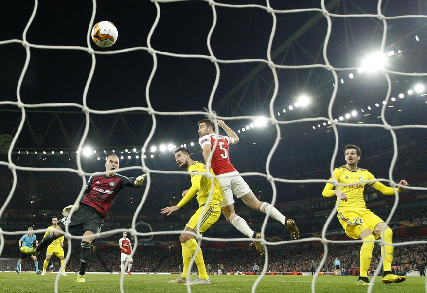 Arsenal's Sokratis Papastathopoulos, second right, scores his side's third goal during the Europa League round of 32 second leg soccer match between Arsenal and Bate at the Emirates stadium in London, Thursday, Feb. 21, 2019. (AP Photo/Matt Dunham)