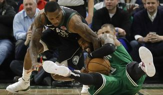 Boston Celtics' Kyrie Irving, right, and Milwaukee Bucks' Eric Bledsoe, left, fight for the ball during the second half of an NBA basketball game Thursday, Feb. 21, 2019, in Milwaukee. (AP Photo/Aaron Gash)