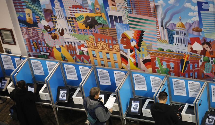 FILE - In this Nov. 6, 2018 file photo voters cast their ballots at the Denver Elections Division in Denver. Colorado's Democrat-controlled Legislature has approved a bill on Thursday, Feb. 21, 2019, to join other states in casting their presidential electoral votes for the winner of the national popular vote. (AP Photo/David Zalubowski, File)