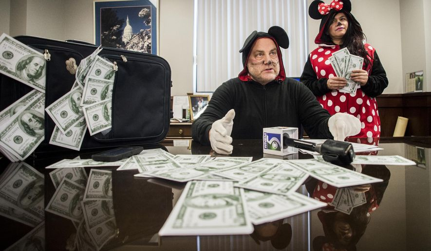 Genesee County Clerk-Register John Gleason, center, alleges that a recent trip county employees took to the Disney Institute in Florida was improper so he dressed up like Mickey Mouse to prove his point on Feb. 20, 2019, in Flint, Mich. (Jake May/MLive.com/The Flint Journal via AP)