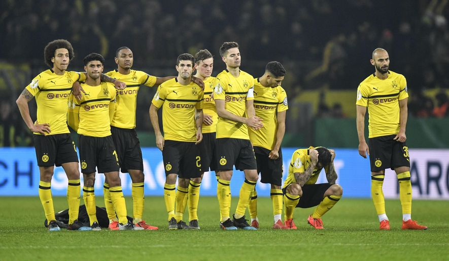 FILE -- In this Tuesday, Feb. 5, 2019 photo Dortmund's Paco Alcacer, 2nd from right, looks down after he missed to score the first penalty during the shootout at the German soccer cup, DFB Pokal, match between Borussia Dortmund and Werder Bremen in Dortmund, Germany. Borussia Dortmund hasn't had a run of five games without a win since Peter Bosz was in charge in 2017. On Sunday, the Dutch coach will attempt to prolong his former side's misery when his Bayer Leverkusen side visits the Bundesliga leaders for a game that could have serious implications for the title. (AP Photo/Martin Meissner, file)