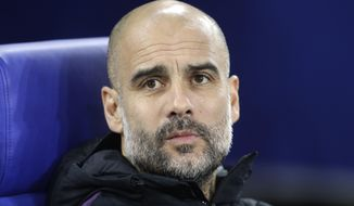 Manchester City coach Pep Guardiola takes his seat prior to the first leg, round of sixteen, Champions League soccer match between Schalke 04 and Manchester City at Veltins Arena in Gelsenkirchen, Germany, Wednesday Feb. 20, 2019. (AP Photo/Michael Probst)