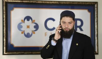 Hassan Shibly, attorney for Hoda Muthana, the Alabama woman who left home to join the Islamic State group in Syria, speaks on a phone before a news conference Wednesday, Feb. 20, 2019, in Tampa, Fla. United States Secretary of State Mike Pompeo said Muthana is not a U.S. citizen and will not be allowed to return to the United States. (AP Photo/Chris O'Meara)