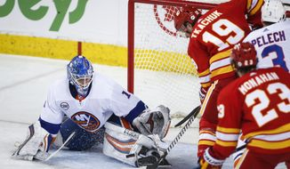 New York Islanders goalie Thomas Greiss, left, of Germany, stops a shot from Calgary Flames' Matthew Tkachuk during the second period of an NHL hockey game Wednesday, Feb. 20, 2019, in Calgary, Alberta. (Jeff McIntosh/The Canadian Press via AP)