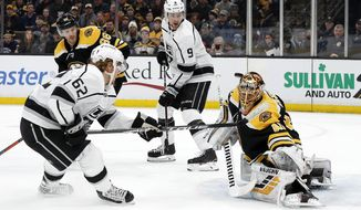 Boston Bruins goaltender Tuukka Rask takes a shot off his mask by Los Angeles Kings' Carl Hagelin (62) off his mask during the this period of an NHL hockey game Saturday, Feb. 9, 2019, in Boston. (AP Photo/Winslow Townson)