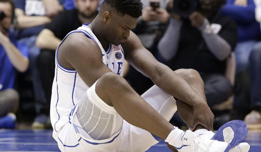 Duke's Zion Williamson sits on the floor following a injury during the first half of an NCAA college basketball game against North Carolina, in Durham, N.C., Wednesday, Feb. 20, 2019. Duke might have to figure out what the Zion Show will look like without its namesake. All because of a freak injury to arguably the most exciting player in college basketball. As his Nike shoe blew out, Williamson sprained his right knee on the first possession of what became top-ranked Duke's 88-72 loss to No. 8 North Carolina.(AP Photo/Gerry Broome) **FILE**