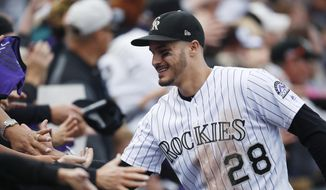FILE - In this Sept. 30, 2018, file photo, fans congratulate Colorado Rockies third baseman Nolan Arenado after the Rockies defeated the Washington 12-0, in Denver. The sluggish free agent market the last two years has not scared off Colorado third baseman Nolan Arenado, who could be among the prizes in the 2020 pool. (AP Photo/David Zalubowski, File) **FiLE**