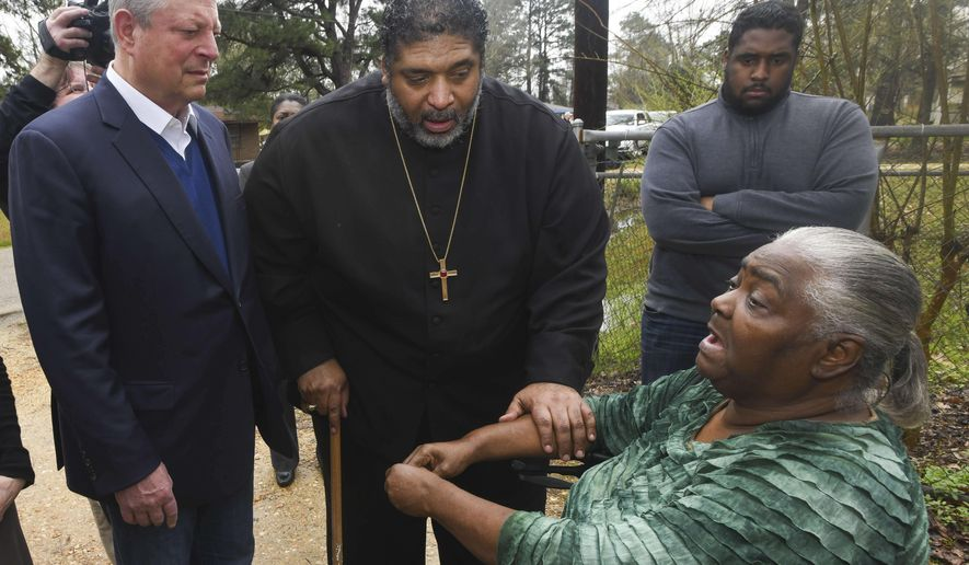 Former Vice President Al Gore, founder of the Climate Reality Project, left to right, and the Rev. William Barber II, leader of the Moral Mondays movement, visit Lowndes County resident Charlie Mae Holcombe to talk about the failing wastewater sanitation system at her home Thursday, Feb. 21, 2019, in Hayneville, Ala. (AP Photo/Julie Bennett)