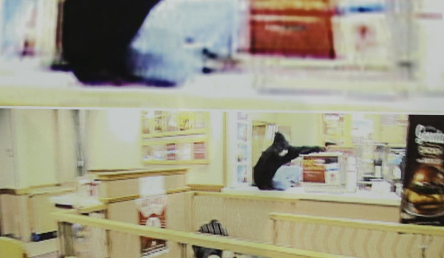 """FILE - In this Aug. 27, 2014 frame grab from security video showing an armed robbery at a Wendy's restaurant in Omaha is displayed during a news conference at police headquarters in Omaha, Neb.  The City of Omaha is on trial in the fatal shooting by police of a television crew member who worked on the law enforcement show """"Cops.""""  Sound technician Bryce Dion was killed in August 2014 when police responded to an armed robbery in an Omaha restaurant. A lawyer for Dion's family said Wednesday, Feb. 20, 2019  that officers fired at robbery suspect Cortez Washington as many as 39 times. One of those bullets inadvertently hit Dion.  (Omaha Police via AP)"""