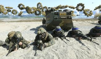 In this March 12, 2016, photo, Marines of the U.S., left, and South Korea, wearing blue headbands on their helmets, take positions after landing on a beach during the joint military combined amphibious exercise, called Ssangyong, part of the Key Resolve and Foal Eagle military exercises, in Pohang, South Korea. (Associated Press) **FILE**
