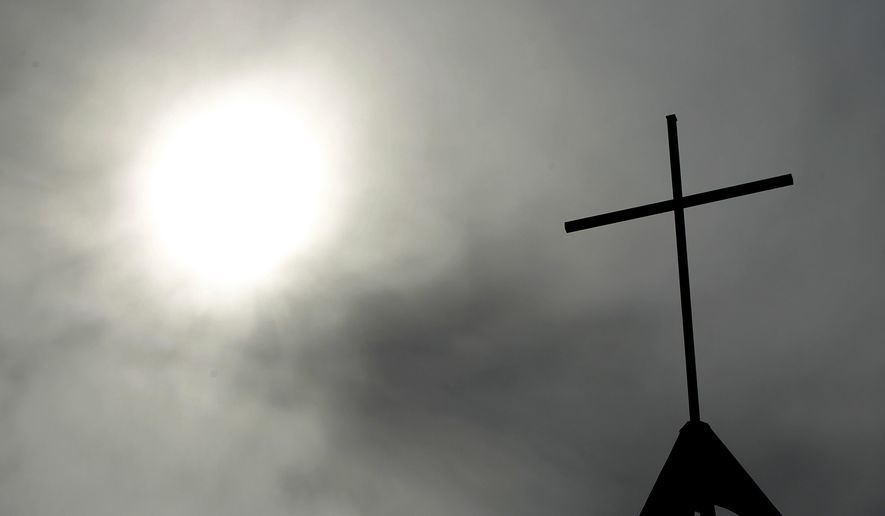 FILE - In this April 8, 2010 file photo a cross sits on top of a church in Berlin, Germany. In September 2018, the German Catholic Church released a devastating report that concluded at least 3,677 people were abused by clergy between 1946 and 2014.  Pope Francis' high-stakes sex abuse prevention summit is meant to call attention to the crisis as a global problem that requires a global response. (AP Photo/Markus Schreiber, File)