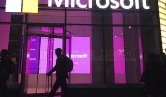 """In this Nov. 10, 2016, file photo, people walk near a Microsoft office in New York. A group of Microsoft workers is demanding the company cancel a contract supplying U.S. Army soldiers with HoloLens headsets that could help them spot adversaries on the battlefield. A letter signed by more than 50 employees Friday, Feb. 22, 2019, says they """"refuse to create technology for warfare and oppression."""" (AP Photo/Swayne B. Hall, File)"""