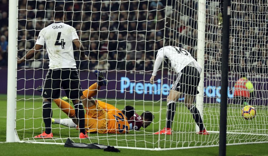 West Ham's Chicaharito, second right, scores his side's opening goal during the English Premier League soccer match between West Ham and Fulham at the London Stadium in London, Friday, Feb. 22, 2019. (AP Photo/Matt Dunham)